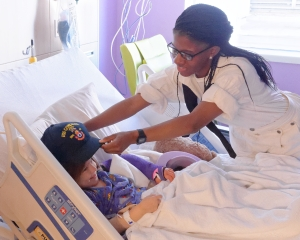 160422-N-NW169-002 SAN ANTONIO (April 22, 2016) Gunner's Mate Seaman Johnelle Jones, assigned to USS Constitution, presents a Navy command ball cap to a patient at Children's Hospital of San Antonio during a Caps for Kids visit. The Sailors from Old Ironsides are participating in San Antonio's Navy Week. The Navy Week program is designed to raise awareness about the Navy in areas across the country that traditionally do not have a naval presence, and to bring America's Navy closer to the people it protects through community relations projects, speaking engagements, science, technology, engineering, mathematics (STEM) demonstrations and media interviews with flag hosts and local area Sailors. (U.S. Navy photo by Chief Mass Communication Specialist Michael O'Day/Released)